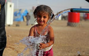 a young girl is playing with water in a refugee camp