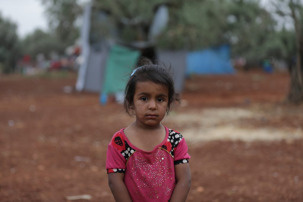 A young girl stands outside