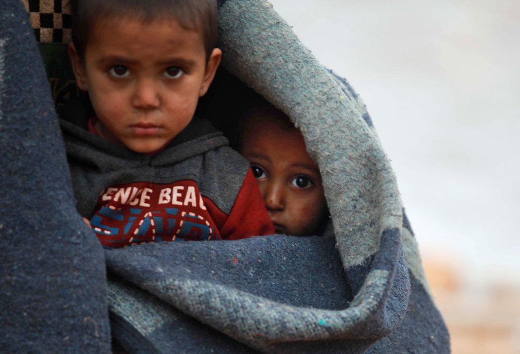 Syrian children huddle under blanket