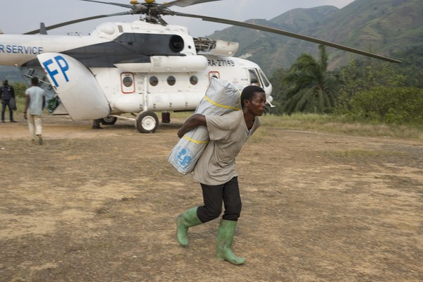 a boy carries a UNICEF pack on his back in front of an helicopter