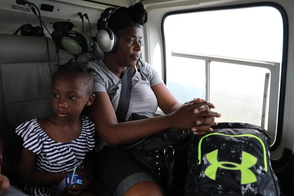 A young girl and her mother are sitting in a helicopter