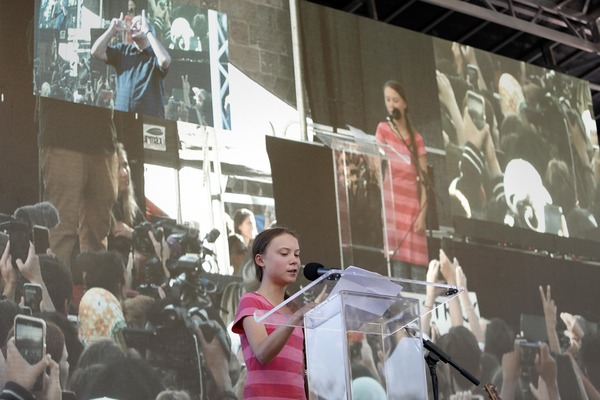 A teenage girl is giving a speech in front of thousands of people