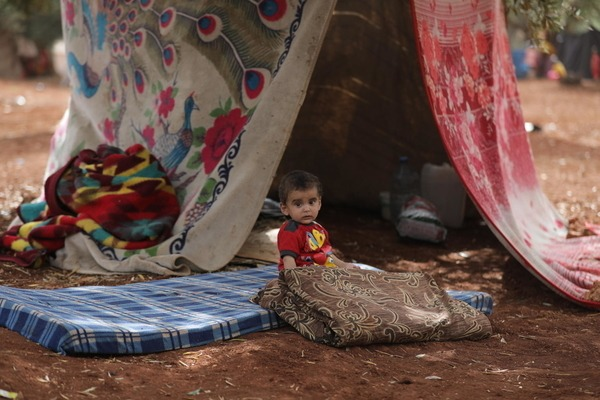 a  young boy is sitting on a mattress in front of a tent