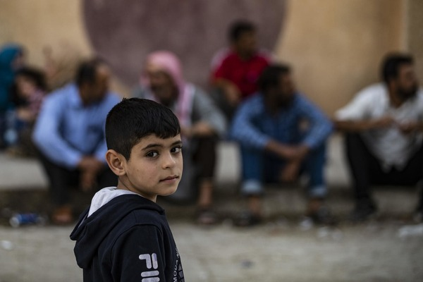 a boy stands in the street in front of men sitting
