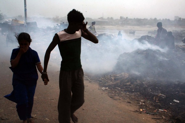 A boy is holding the hand of a little girl in front of a burning area