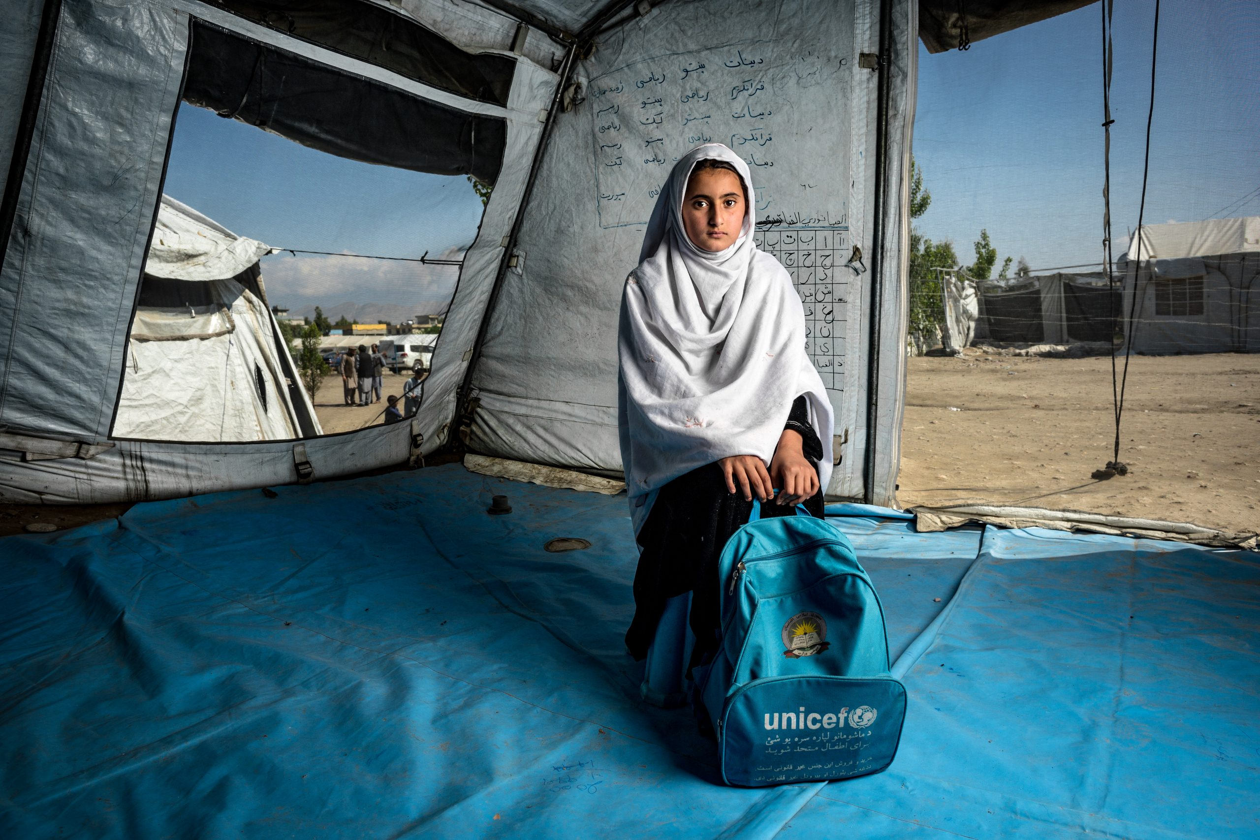 a girl is sitting in an UNICEF tent holding an UNICEF backpack