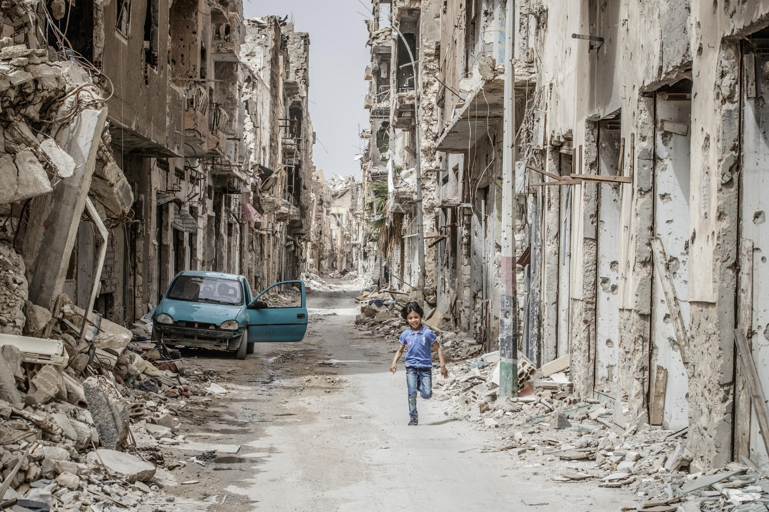 A child runs through the debris in a destroyed town