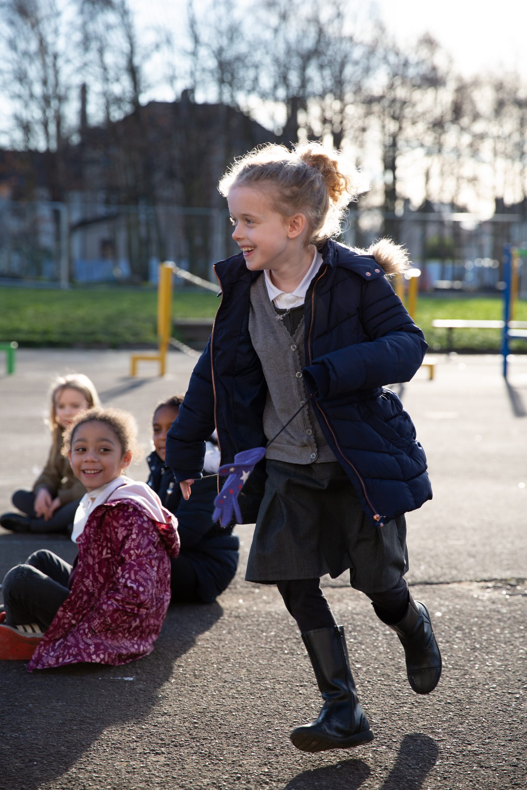 a young girl is running around her friends in a playground