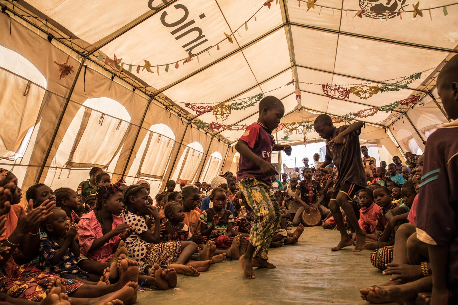 Children are dancing in an UNICEF tent