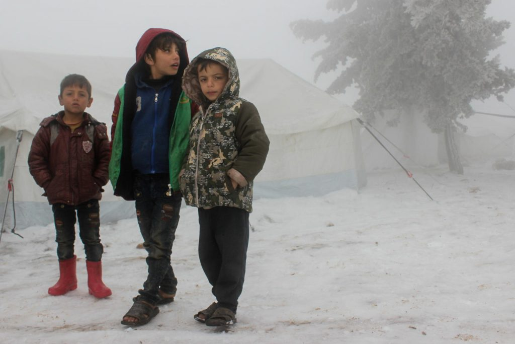 Three Boys are standing together under a snow blizzard