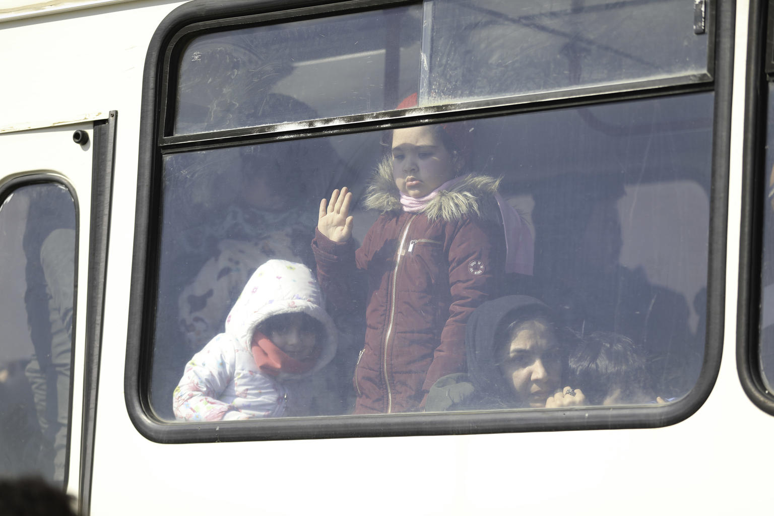 Child looking out from the window of a bus