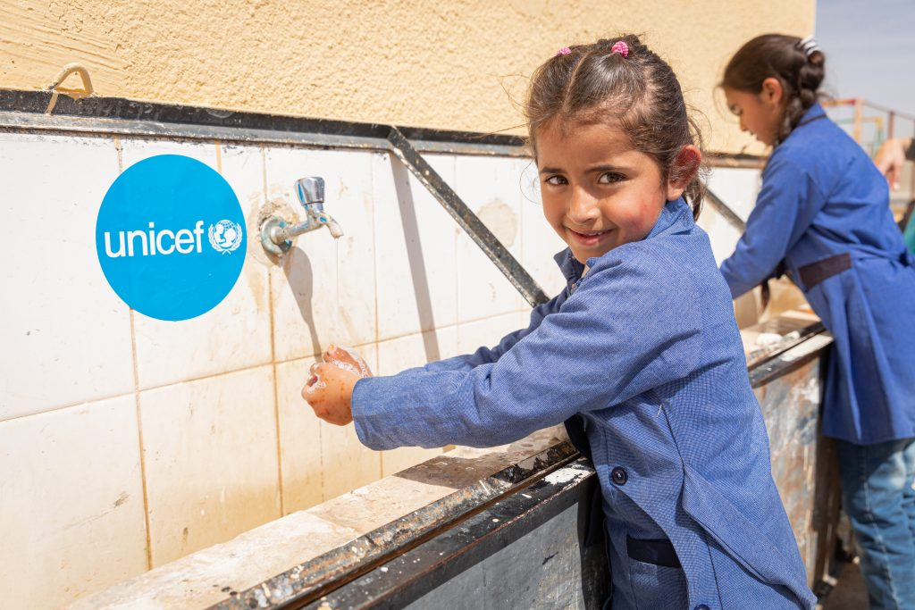 young girl is washing her hands in a refugee camp