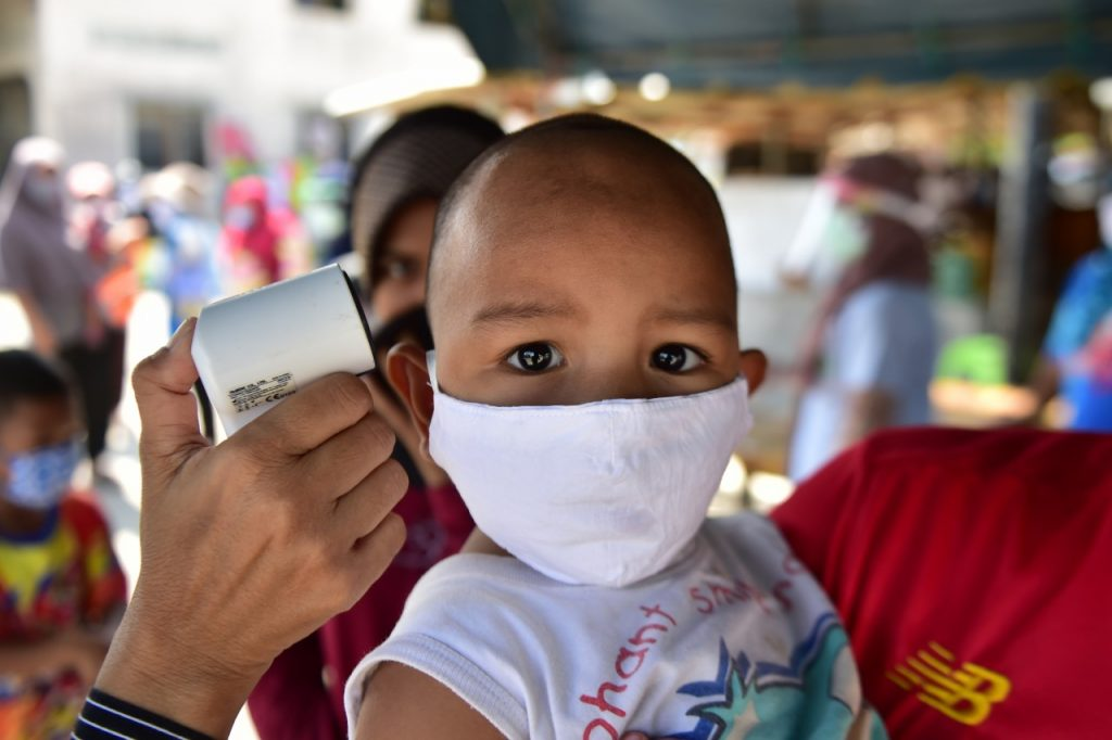 A young child wearing a face mask has a temperature check