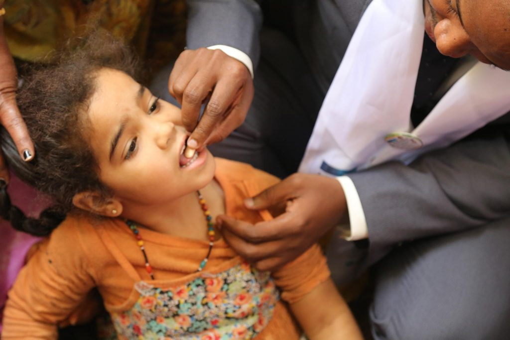 girl being given vitamin a supplement