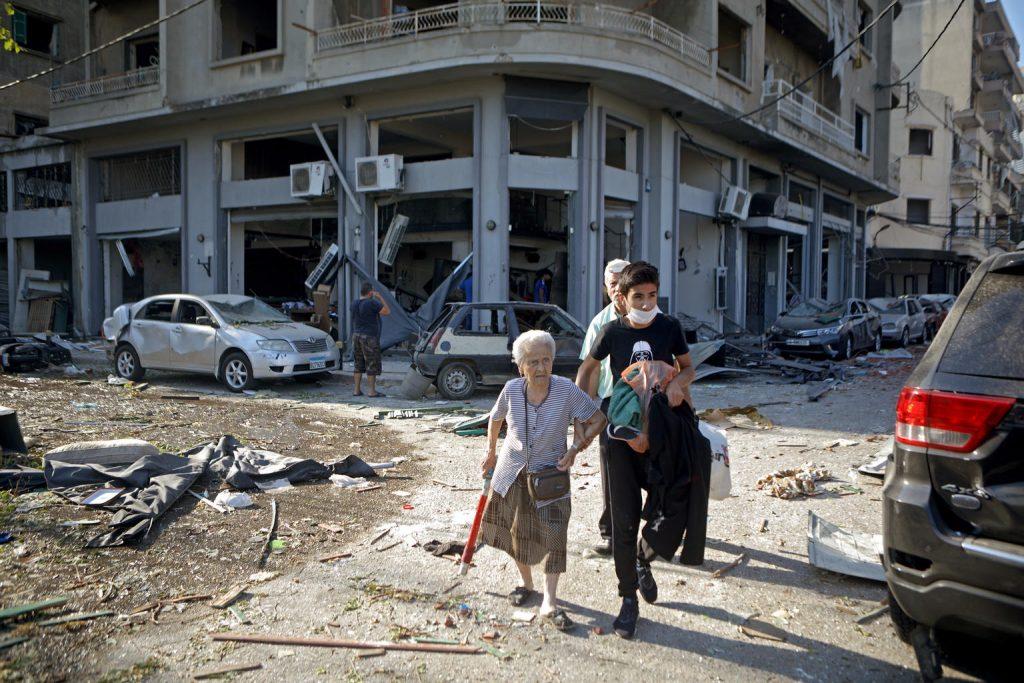 woman walking amongst rubble in beirut