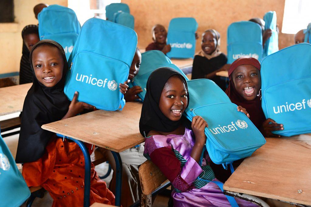 girls holding unicef school bags