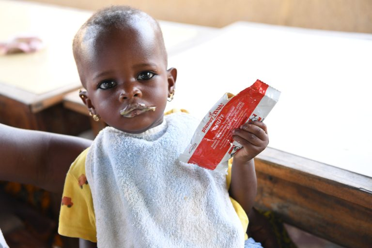 A young child is eating peanut paste