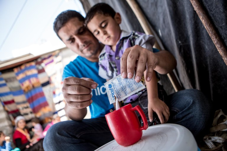 Iraq, May 2013. UNICEF worker Abduljabar prepares oral rehydration salts for four year old Ahmed. Ahmed lives with his brother and parents in a small room amongst five other families in the Domiz refugee camp in Northern Iraq. Domiz is situated near the city of Dohuk, about forty miles from the Syrian border. Approximately 40,000 Syrians are living here, in facilities provided for around half that number. April 2013 marked one year since Domiz camp opened in Dohuk, Northern Iraq. In that time it has grown to a tent city of nearly 40,000 Syrian refugees. UNICEF provides services in education, child protection, water, sanitation and hygiene, and health and nutrition. UK Nat Com local copies of these files at \Unicef-mediaphotosCOUNTRIESsyriaSY2013-refugees-IRAQ