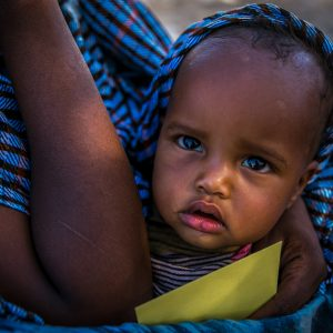 Sadra Ubox 9 months old is carried by her mother holding a registration medical card for the infant in Shinile sub-district which has been particularly hard hit by a drought in Ethiopia.