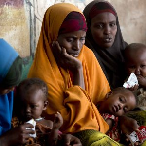 On 1 February, women feed their young children ready-to-use therapeutic food at a UNICEF-supported outpatient therapeutic feeding clinic in Somalia.