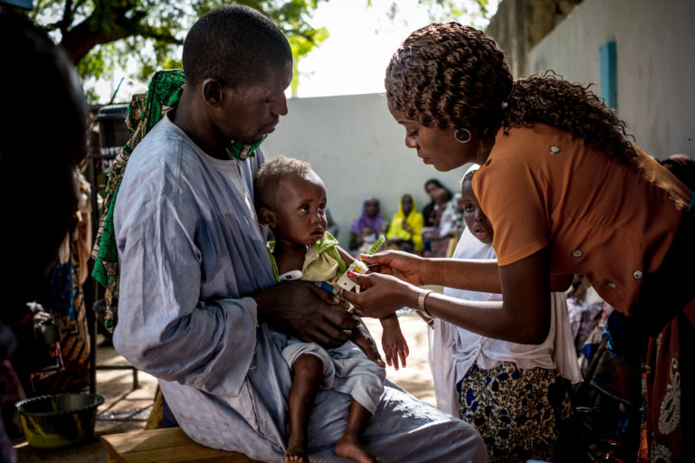 A medical practitioner uses a mid upper arm circumference measuring tape on a child at the Dalaram health and malnutrition clinic run by the government and supported by UNICEF in Borno State, Nigeria,