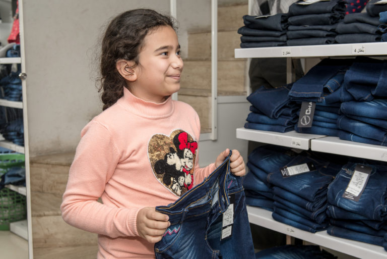 "On 22 January, 10 year-old Leen came with her mother to a pre-selected shop in Tartous to pick out new winter clothes. ""I still don't know what I want to buy,"" she said. ""I'm checking all the colors and styles to choose the ones I like the most,"" she added with a grin. The e-vouchers give parents flexibility in choosing the right items and sizes for their children. It also contributes to their empowerment and sense of dignity while supporting the local economy by creating demand for local suppliers. Location: Tartous & Lattakia, Syria Date: 22-24 January 2017 As temperatures drop, UNICEF continues the distribution of e-vouchers to vulnerable families in the coastal cities of Tartous and Lattakia in Syria. Families of 12,000 children in the two cities will receive vouchers similar to ATM cards, redeemable at selected shops, to buy a full set of winter clothes for their children. A set includes a jacket, a woolen sweater, a thermal outfit, warm winter trousers, woolen hat, scarf, gloves, socks and a pair of winter boots. UNICEF provides each selected shop with a mobile phone and a Bluetooth printer, which allows them to place the orders of beneficiaries, apply the transactions and update their database of available items. As prices, inflation and unemployment increase, families in Syria are unable to afford the most basic items like warm clothing for their children. In particular, displaced children living in shelters have no protection from the cold. The e-vouchers give parents flexibility in choosing the right items and sizes for their children. It also contributes to their empowerment and sense of dignity while supporting the local economy by creating demand for local suppliers."