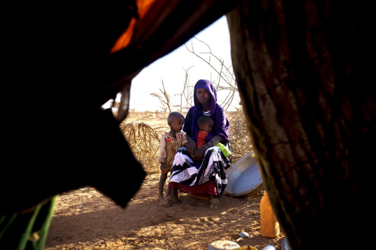 Sara Fara Mohamud sits for a photograph with her two young children who are suffering from flu and diarrhoea outside their makeshift shelter near the town of Burao, Somalia, Wednesday 8 March 2017. Sara has medicine for her two children, but no food. She was forced to leave her home and come to Burao in search of food and water. As the humanitarian situation in Somalia continues to deteriorate in early 2017, an estimated 6.2 million people (about half of the population) are either severely food insecure or in need of livelihood support. Severe drought is now affecting all regions, following the failure of two or more consecutive rains, and with the last 'Deyr' season (October-December) performing poorly and large areas receiving less than 40 percent normal rainfall. The ongoing drought and other shocks have left communities with little or no remaining resources. Entire villages have lost their crops or seen their livestock die. The prices for water and locally produced food have risen dramatically, and thousands of people are on the move in search of food and water. The drought is also exacerbating the existing nutrition crisis in the country, where more than 363,000 children under the age of 5 are acutely malnourished, including 71,000 suffering from severe acute malnutrition (SAM) and in urgent need of life-saving treatment. UNICEF estimates that by April 2017, 750,000 people will need health assistance and 4.5 million will need water, sanitation and hygiene (WASH) support. Also, should the next rains prove inadequate and humanitarian assistance not reach drought-affected populations, there is a risk of famine in the second half of 2017. The drought has also led to an increase in waterborne diseases, with more than 4,000 cases of acute watery diarrhoea/cholera this year. UNICEF and the World Food Programme are working together to scale up their responses in accessible areas, where millions of lives are at risk. Joint efforts include providing food and water