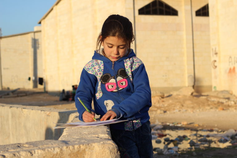 """Huda, 6, draws at a UNICEF-supported child friendly space at a shelter for families displaced by the ongoing violence in eastern Aleppo city, in the Jibreen area on the outskirts of Aleppo city, Syrian Arab Republic, Friday 9 December 2016. """"I wish I have a house that has a room only for me. I wish I have my own bed and my own chair,"""" says Huda, who arrived with her family at a shelter in Jibreen a week ago, where she has to share a blanket and a mattress with her four siblings. Huda and many other children like her are staying in a warehouse that now serves as a temporary shelter. No child is spared the horror of the war in the Syrian Arab Republic, where children come under attack on a daily basis. Violence is everywhere, ripping apart places that children thought were safe - places that should be safe: schools, hospitals, playgrounds, public parks and children's own homes. Children have paid the heaviest price in this six-year war and their suffering hit rock bottom in 2016 in a drastic escalation of violence, according to a UNICEF report published in March 2017. UNICEF-supported psychosocial support programmes reached 509,857 children in 2016. The programmes, which are designed to help children cope with the horror and trauma they have experienced, encourage children to participate and engage in a range of activities – including drawing. It is through these drawings that the children depict their experiences, as well as their wishes and hopes for a better future."""