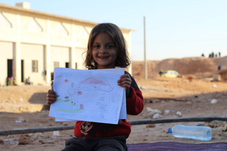 "Ammar, 6, holds up a picture he drew at a UNICEF-supported child friendly space at a shelter for families displaced by the ongoing violence in east Aleppo city in the Jibreen area, on the outskirts of Aleppo city, Syrian Arab Republic, Friday 9 December 2016. ""It is a big clean space with green grass, trees and flowers,"" says Ammar describing his drawing of a house with a large garden. No child is spared the horror of the war in the Syrian Arab Republic, where children come under attack on a daily basis. Violence is everywhere, ripping apart places that children thought were safe - places that should be safe: schools, hospitals, playgrounds, public parks and children's own homes. Children have paid the heaviest price in this six-year war and their suffering hit rock bottom in 2016 in a drastic escalation of violence, according to a UNICEF report published in March 2017. UNICEF-supported psychosocial support programmes reached 509,857 children in 2016. The programmes, which are designed to help children cope with the horror and trauma they have experienced, encourage children to participate and engage in a range of activities – including drawing. It is through these drawings that the children depict their experiences, as well as their wishes and hopes for a better future."