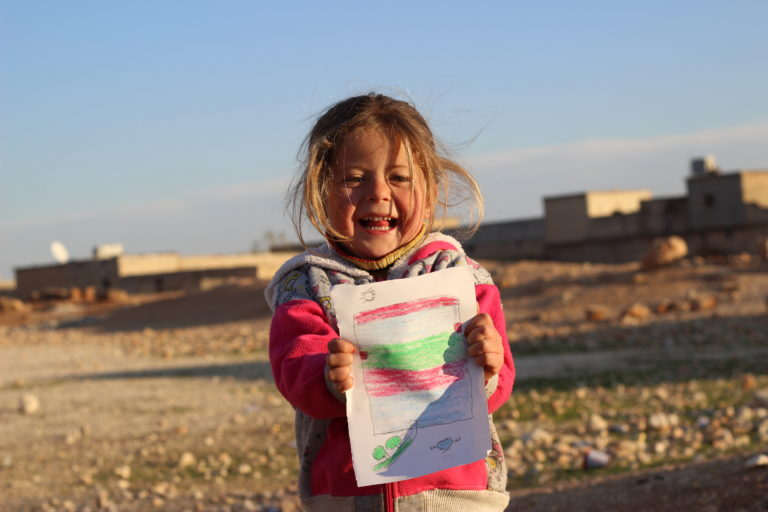 "Fatima, 5, holds up a picture she drew at a UNICEF-supported child friendly space at a shelter for families displaced by the ongoing violence in east Aleppo city in the Jibreen area, on the outskirts of Aleppo city, Syrian Arab Republic, Friday 9 December 2016. ""I want to live in a big house that has room for all my family and friends."" says Fatima. No child is spared the horror of the war in the Syrian Arab Republic, where children come under attack on a daily basis. Violence is everywhere, ripping apart places that children thought were safe - places that should be safe: schools, hospitals, playgrounds, public parks and children's own homes. Children have paid the heaviest price in this six-year war and their suffering hit rock bottom in 2016 in a drastic escalation of violence, according to a UNICEF report published in March 2017. UNICEF-supported psychosocial support programmes reached 509,857 children in 2016. The programmes, which are designed to help children cope with the horror and trauma they have experienced, encourage children to participate and engage in a range of activities – including drawing. It is through these drawings that the children depict their experiences, as well as their wishes and hopes for a better future."