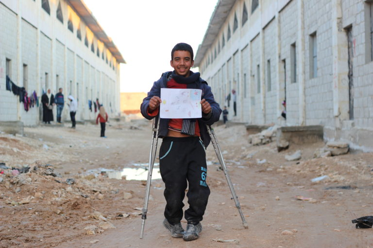 "Khaled, 13, who was injured during heavy fighting in eastern Aleppo, holds up a picture he drew of a big house with a swimming pool, at a shelter for families displaced by the ongoing violence in eastern Aleppo city, in the Jibreen area on the outskirts of Aleppo city, Syrian Arab Republic, Friday 9 December 2016. ""I love sport, especially swimming. I wish I learn how to swim and be a fast swimmer,"" says Khaled. Living under siege, many children like Khaled spent months hiding in dark basements or in underground rooms, lacking the safety the needed to even play. No child is spared the horror of the war in the Syrian Arab Republic, where children come under attack on a daily basis. Violence is everywhere, ripping apart places that children thought were safe - places that should be safe: schools, hospitals, playgrounds, public parks and children's own homes. Children have paid the heaviest price in this six-year war and their suffering hit rock bottom in 2016 in a drastic escalation of violence, according to a UNICEF report published in March 2017. UNICEF-supported psychosocial support programmes reached 509,857 children in 2016. The programmes, which are designed to help children cope with the horror and trauma they have experienced, encourage children to participate and engage in a range of activities – including drawing. It is through these drawings that the children depict their experiences, as well as their wishes and hopes for a better future."
