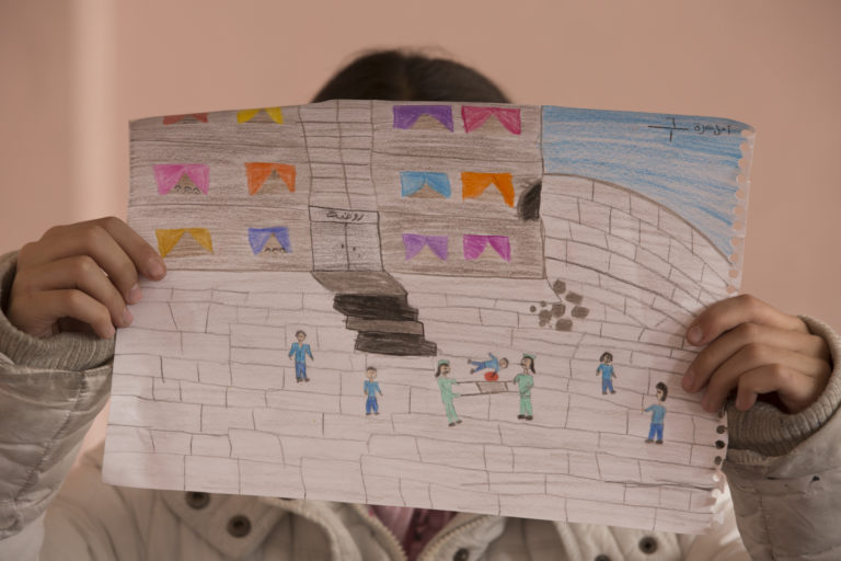 "Amal, 12, holds up a picture she drew as a tribute for the children of a kindergarten in Harasta, a besieged town in rural Damascus, which she heard was attacked, at the Bakri Kaddoura school, Damascus, Syrian Arab Republic, Thursday 10 November 2016. ""I keep thinking of the little children, I bet they didn't even know what was happening when their kindergarten was hit by a shell."" No child is spared the horror of the war in the Syrian Arab Republic, where children come under attack on a daily basis. Violence is everywhere, ripping apart places that children thought were safe - places that should be safe: schools, hospitals, playgrounds, public parks and children's own homes. Children have paid the heaviest price in this six-year war and their suffering hit rock bottom in 2016 in a drastic escalation of violence, according to a UNICEF report published in March 2017. UNICEF-supported psychosocial support programmes reached 509,857 children in 2016. The programmes, which are designed to help children cope with the horror and trauma they have experienced, encourage children to participate and engage in a range of activities – including drawing. It is through these drawings that the children depict their experiences, as well as their wishes and hopes for a better future."
