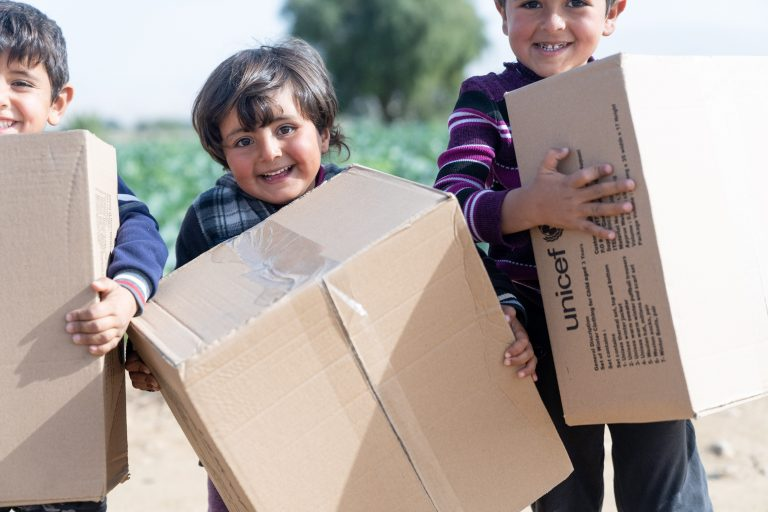 Three children are holding boxes