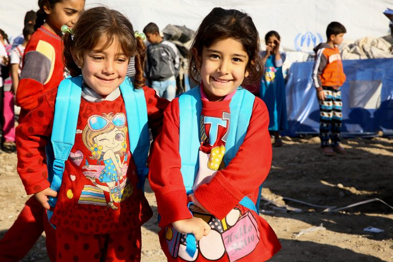 Two little girls are standing in front of a camera wearing UNICEF backpacks
