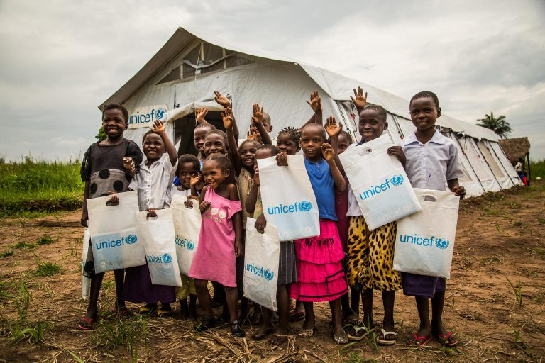 a group of children is standing in front of a tent holding UNICEF plastic bags